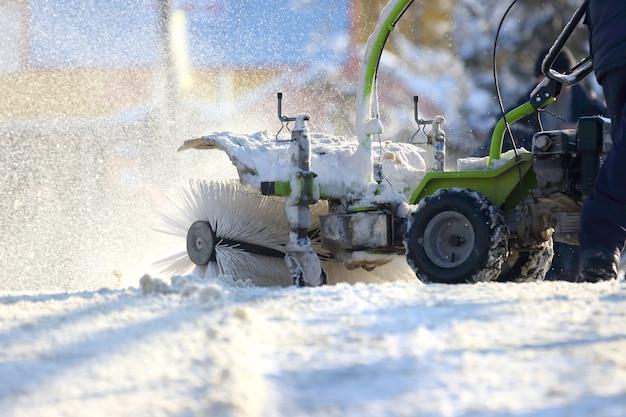 Uomo che pulisce la strada da neve trattore manuale speciale Foto Premium