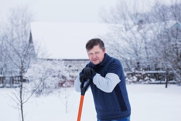 L'uomo pulisce la pala da neve Foto Premium