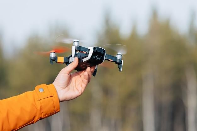 Un uomo in abiti con una manica arancione tiene in mano un drone quadricottero volante. Foto Premium