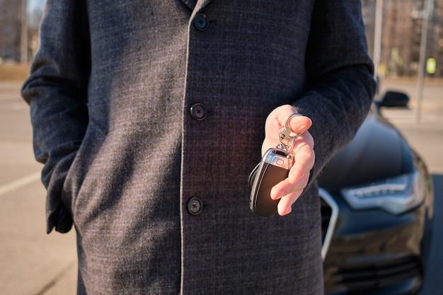 Un uomo in un cappotto detiene le chiavi sullo sfondo di un'auto moderna. concetto di noleggio. Foto Premium