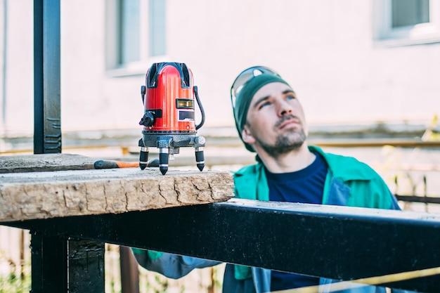 Un uomo in un cantiere controlla il lavoro con una livella laser Foto Premium
