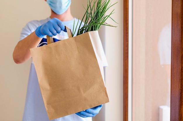 Uomo che consegna generi alimentari ordinati online Foto Premium