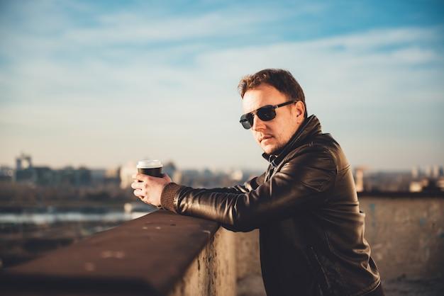 Uomo che beve il caffè sul tetto Foto Premium