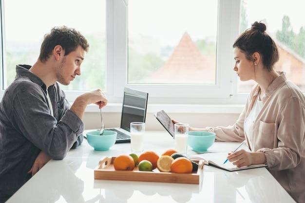 L'uomo che mangia cereali e usando un laptop sta guardando sua moglie che beve latte e scrive qualcosa Foto Premium
