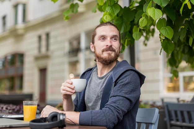 Uomo che gode del caffè in una terrazza della città Foto Premium