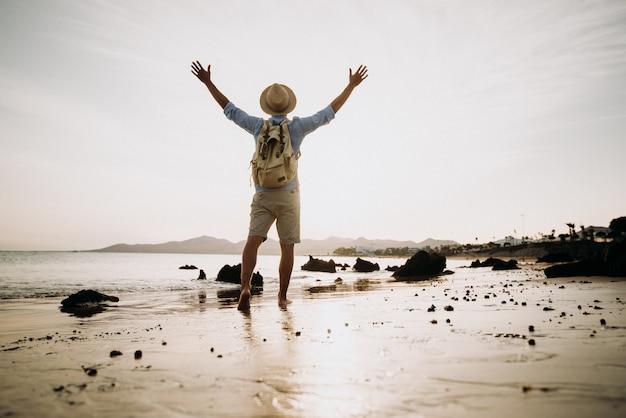Uomo che gode della vita e della libertà aprendo le braccia al cielo in spiaggia al tramonto. Foto Premium