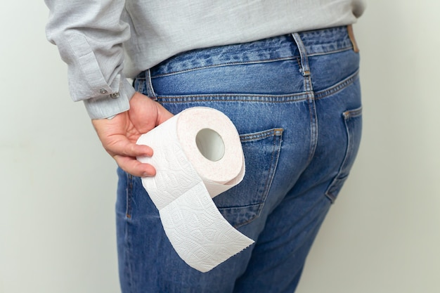Uomo che sente dolore e che tiene il primo piano del rotolo di carta igienica. diarrea, emorroidi o concetto di costipazione Foto Premium