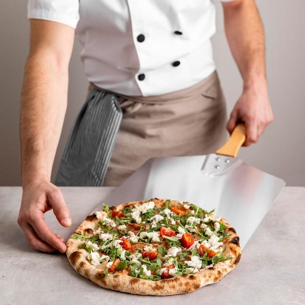 Uomo che afferra la pizza con lo strumento di buccia Foto Premium