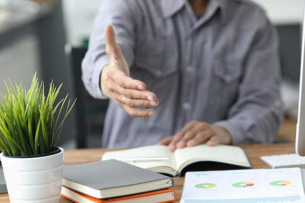 L'uomo in camicia grigia dà la mano come ciao in primo piano dell'ufficio. amico benvenuto mediazione offerta introduzione positiva grazie gesto vertice partecipazione approvazione motivazione contrattazione braccio maschio Foto Premium