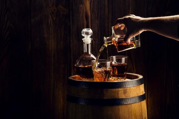Equipaggi la mano che versa la bevanda alcolica in un vetro Foto Premium