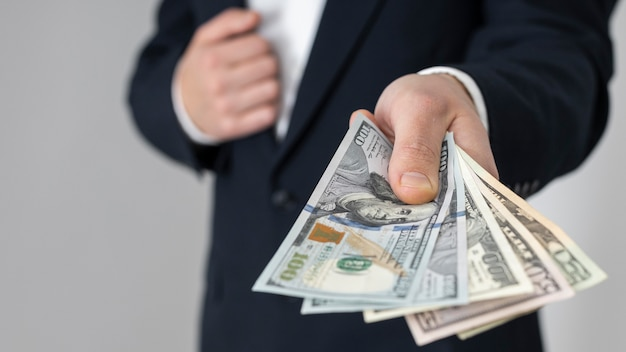 Uomo che passa un mucchio di banconote in dollari Foto Premium