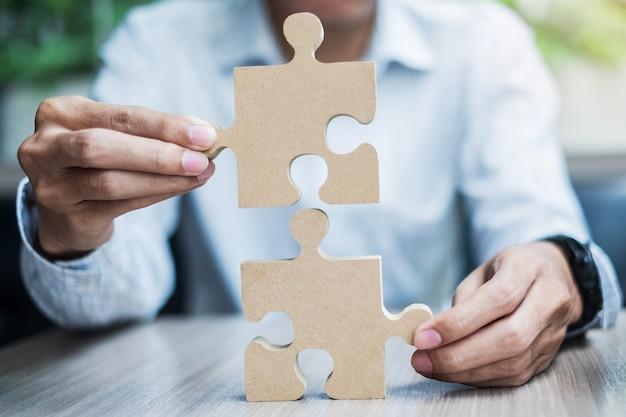 Equipaggi le mani che collegano il puzzle delle coppie sopra la tavola, uomo d'affari che tiene il puzzle di legno dentro l'ufficio. soluzioni aziendali, missione, target, successo, obiettivi e concetti di strategia Foto Premium