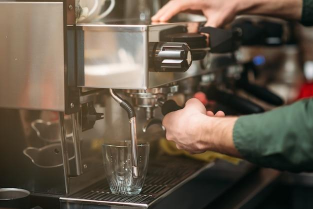 Mani dell'uomo versa il caffè da una macchina per il caffè. Foto Premium