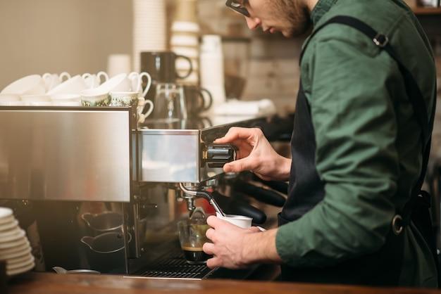 Mani dell'uomo versa la bevanda da una macchina per il caffè. Foto Premium
