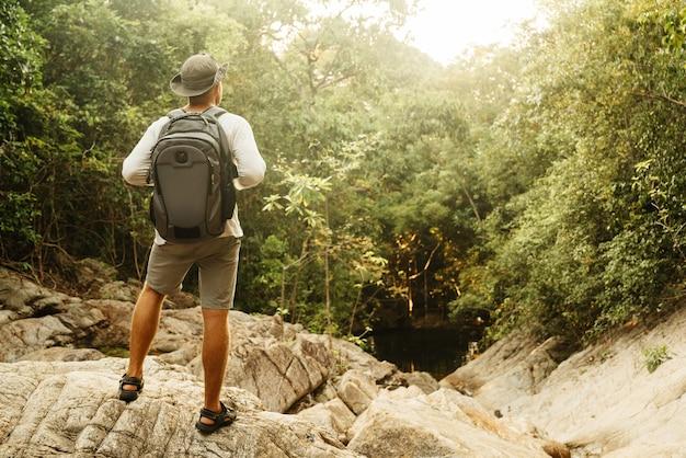 Un uomo con un cappello e pantaloncini con uno zaino è in piedi su una montagna guardando in lontananza in estate. viaggi e romanticismo. Foto Premium