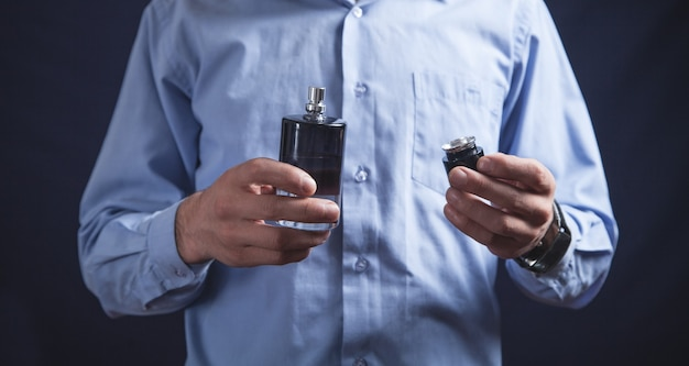 Uomo che tiene una bottiglia di profumo. Foto Premium