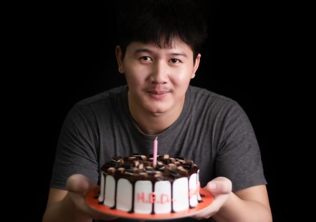 Uomo con gelato al cioccolato torta su tavola in legno rustico su sfondo nero Foto Premium