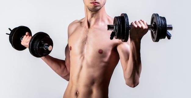 Uomo che tiene il manubrio in mano. ragazzo magro tenere i manubri in mano. Foto Premium