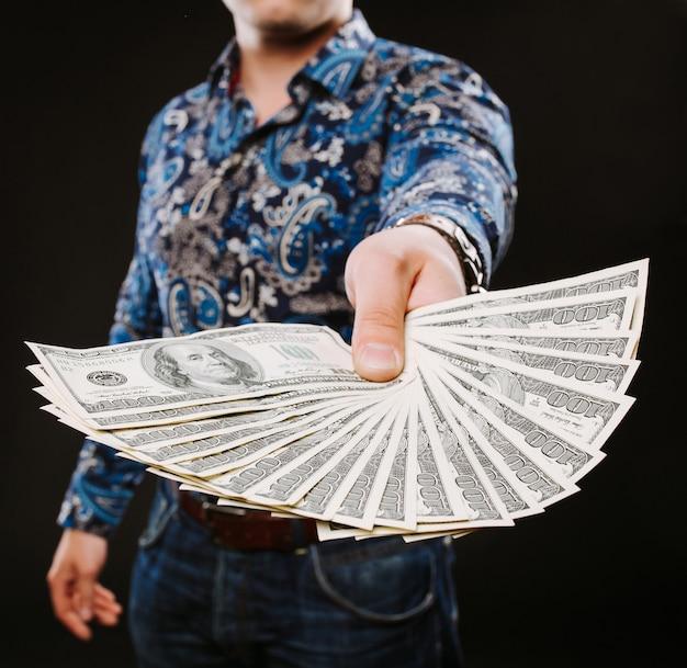 Un uomo in possesso di un fan di banconote in dollari. Foto Premium