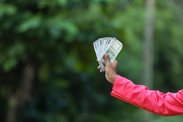 Uomo che tiene in mano nota di denaro indiano Foto Premium