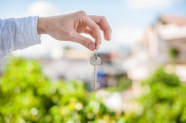 Equipaggi la chiave della tenuta alla casa su fondo delle case nella città. affronta il concetto immobiliare Foto Premium