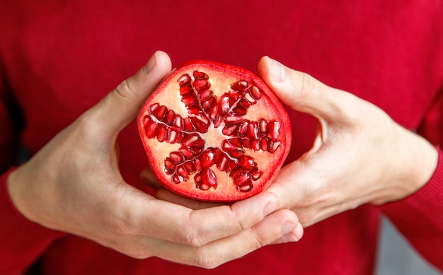 Uomo che tiene e mostrando tagliato melograno maturo. i frutti di melograno sono ricchi di zuccheri, tannini, vitamina c. Foto Premium