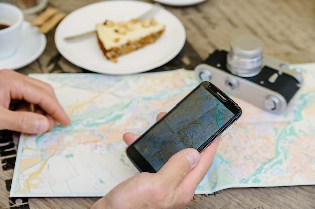 Uomo che tiene uno smartphone lì vicino una macchina fotografica d'epoca, una mappa, un caffè e una torta Foto Premium