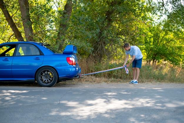 L'uomo che tiene una fune di traino e lo installa sul gancio dell'auto, l'incidente d'auto e il problema con il motore Foto Premium
