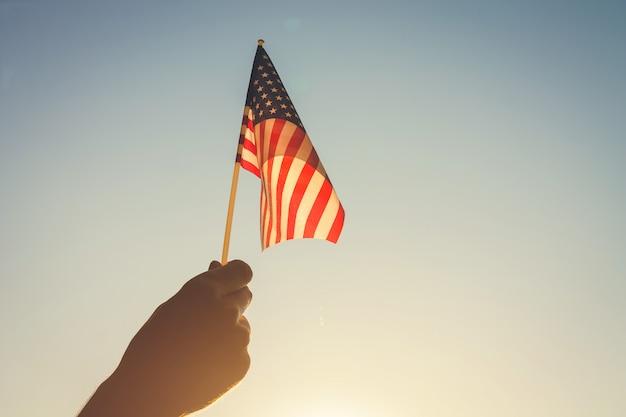 Uomo che tiene la bandiera usa. celebrando l'independence day of america Foto Premium