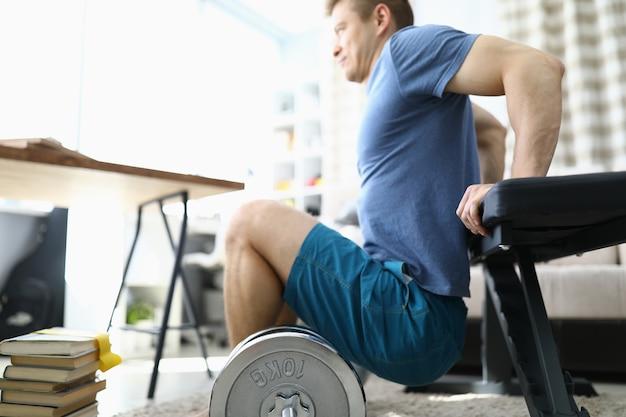 L'uomo sta facendo esercizi fisici a casa del primo piano Foto Premium