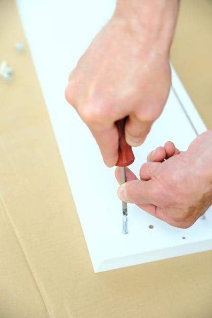 Un uomo sta installando i bulloni del connettore di giunzione nel pannello del mobile. Foto Premium