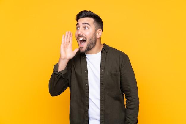 Uomo su sfondo giallo isolato che grida con la bocca spalancata Foto Premium