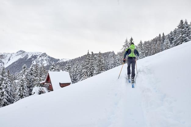 Un uomo in un tour sciistico solitario nelle alpi Foto Premium