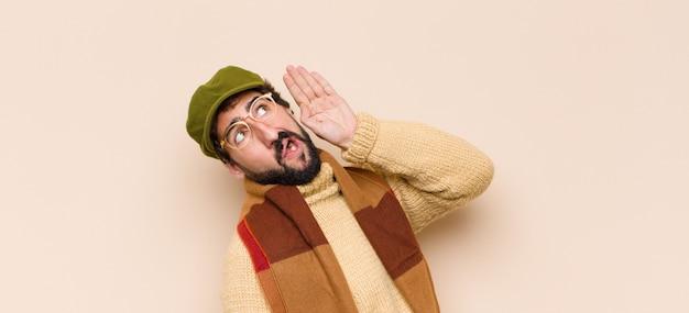 L'uomo sembra serio e curioso, ascolta, cerca di ascoltare una conversazione segreta o gossip, origliare Foto Premium