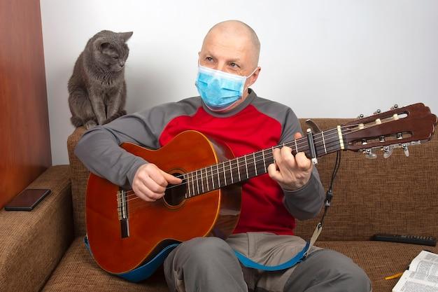 Un uomo con una maschera medica a casa in quarantena a causa di un'epidemia di coronavirus suona una chitarra classica accanto a un gatto grigio Foto Premium