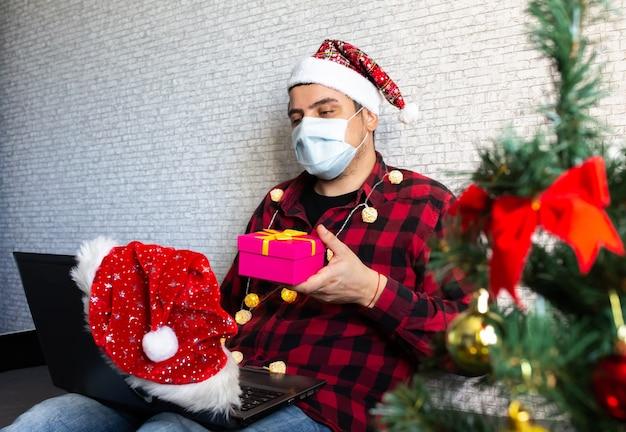 Uomo in maschera medica che condivide i regali della scatola tramite videochiamate Foto Premium