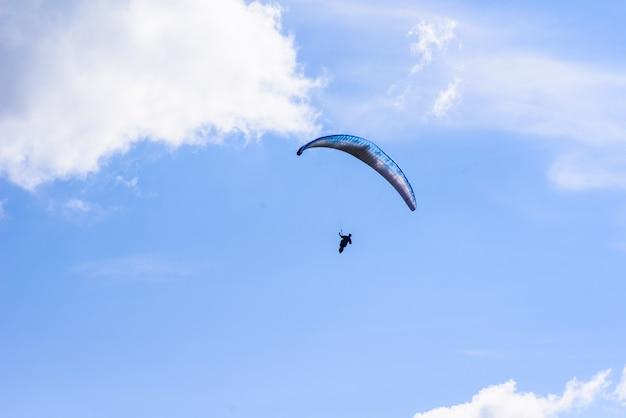 Uomo su un paracadute che vola in chiaro cielo Foto Premium