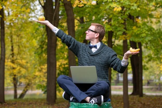 Un uomo su un piedistallo che finge di essere una statua nella posa di un filosofo prima di scegliere una mela o una banana nel parco. Foto Premium