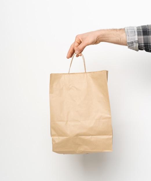 Uomo in camicia a quadri manica intrecciata mano che tiene il sacchetto di carta marrone isolato sul muro bianco Foto Premium