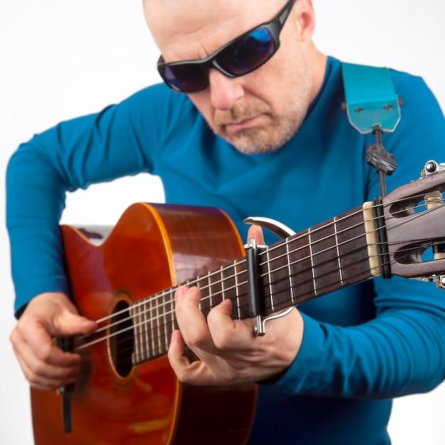 L'uomo suona la chitarra classica su uno sfondo bianco. creatività musicale. strumento musicale a corde Foto Premium