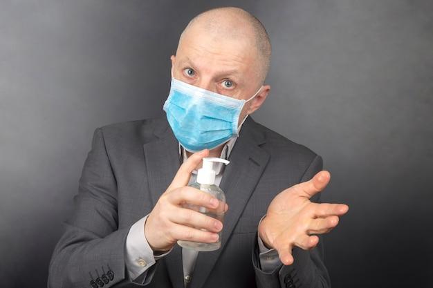 L'uomo in una maschera medica protettiva durante la quarantena disinfetta le mani Foto Premium