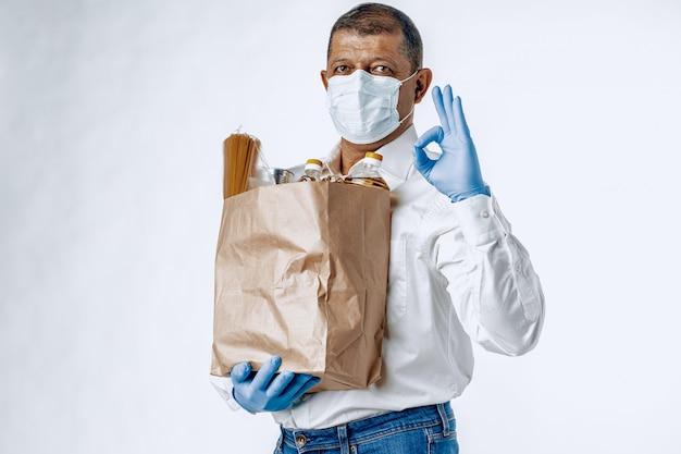 Uomo in una mascherina medica protettiva con una borsa da una drogheria. consegna del cibo Foto Premium