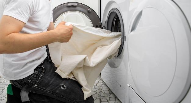 L'uomo mette il bucato in una lavatrice automatica Foto Premium