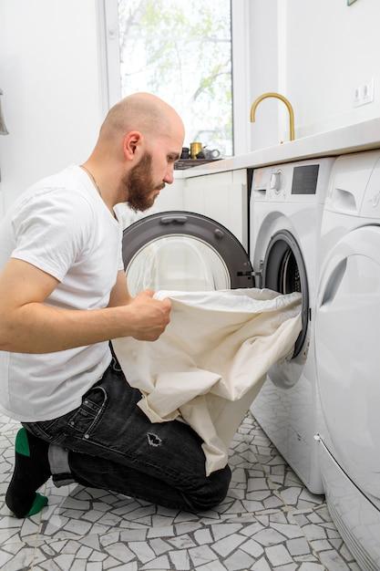 L'uomo mette il bucato in una lavatrice Foto Premium