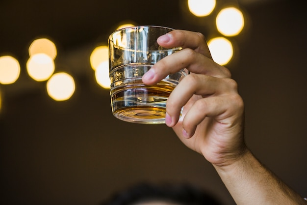 Equipaggi l'innalzamento del pane tostato con il vetro del whiskey sul fondo del bokeh Foto Premium