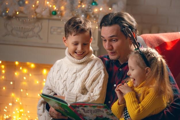 Uomo che legge un libro a un ragazzo e una ragazza Foto Premium