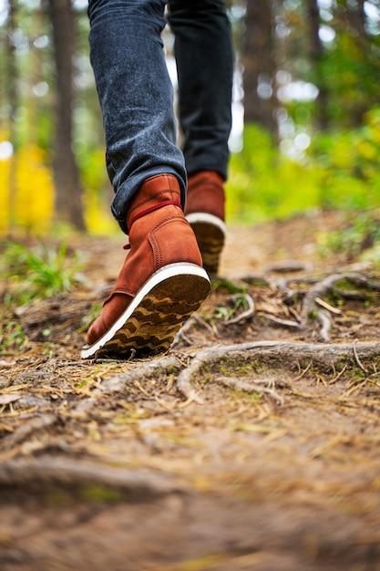 Un uomo con stivali di pelle rossa cammina nella meravigliosa foresta d'autunno. calzature da vicino con copia spase. concetto di viaggio. Foto Premium