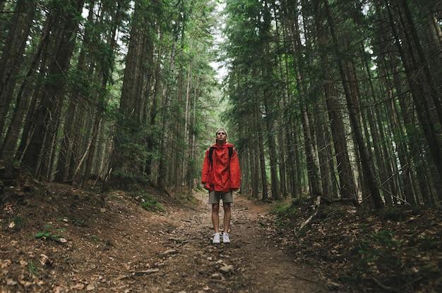L'uomo con un impermeabile rosso si trova su un sentiero in montagna Foto Premium