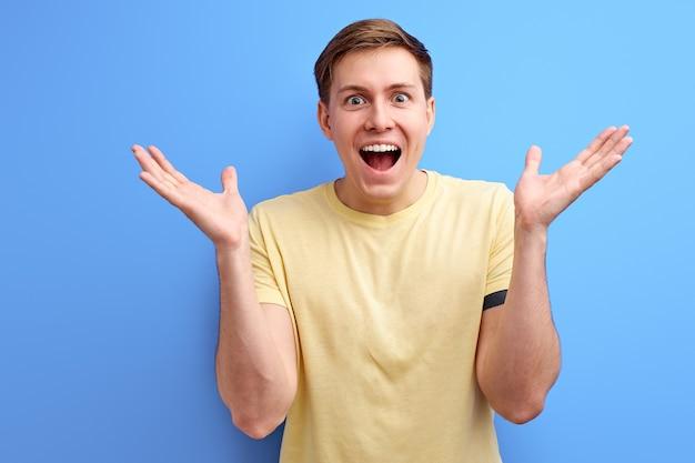 L'uomo si rallegra e celebra la vittoria su sfondo blu, gesticolano maschio positivo di mentalità aperta, alzando le mani e guardando la telecamera con la bocca aperta, ottenere buone notizie Foto Premium