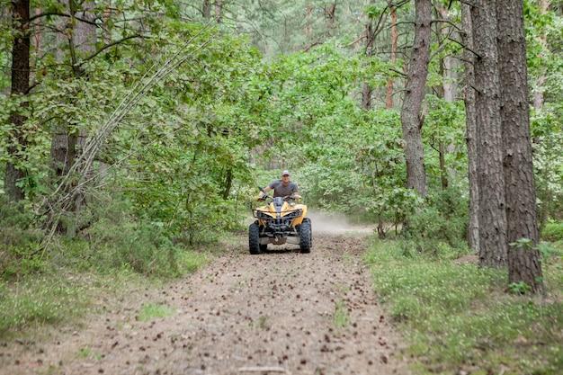 Uomo che guida un quad fuoristrada giallo atv su una foresta sabbiosa. moto estremo, avventura, attrazione turistica. Foto Premium